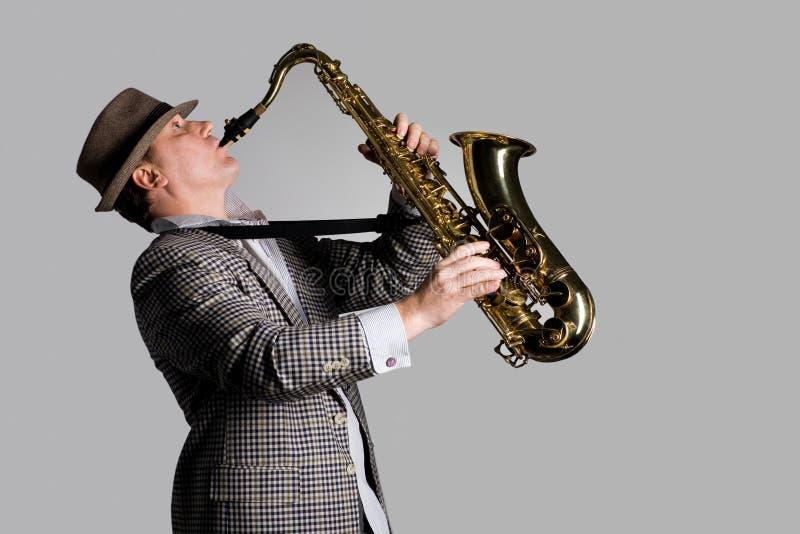 Homem novo que joga o saxofone foto de stock