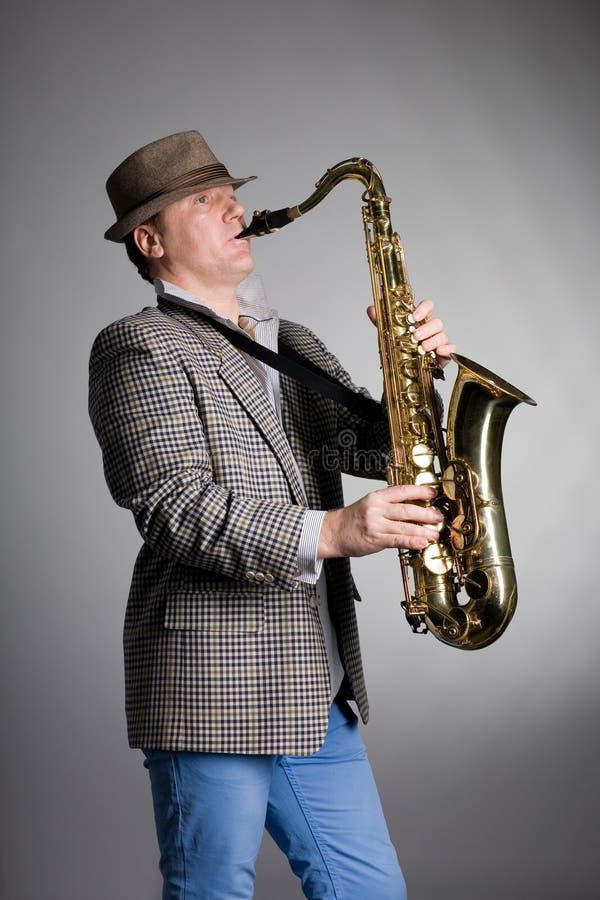 Homem novo que joga o saxofone foto de stock royalty free