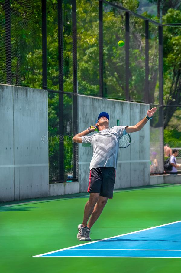 Homem novo que joga o tênis em um dia ensolarado fotos de stock