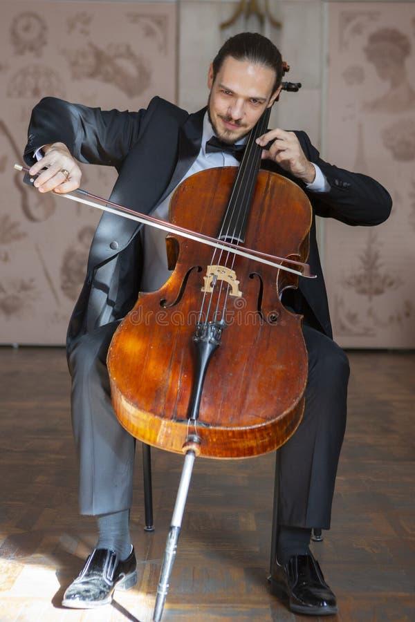 Homem novo que joga o violoncelo Retrato do violoncelista foto de stock