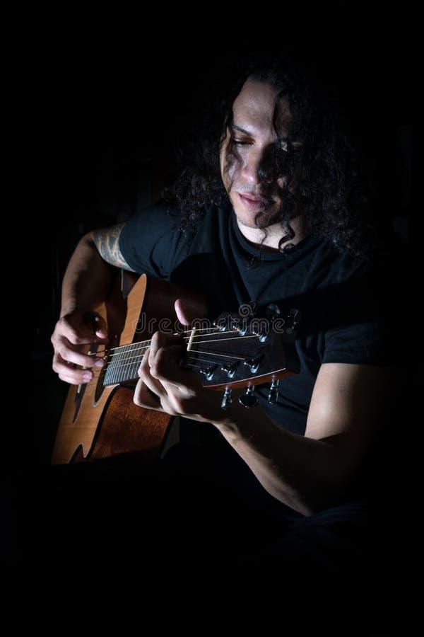 Homem novo que joga uma guitarra imagens de stock royalty free