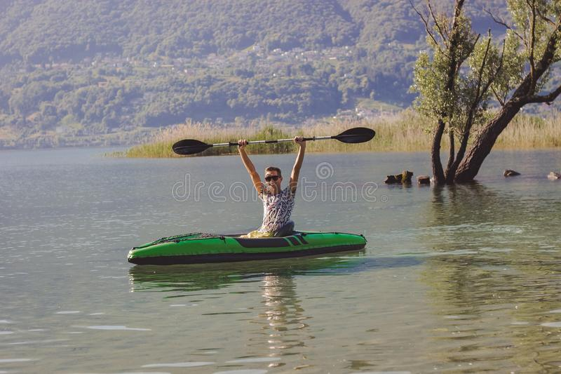 Homem novo que kayaking no lago fotos de stock royalty free