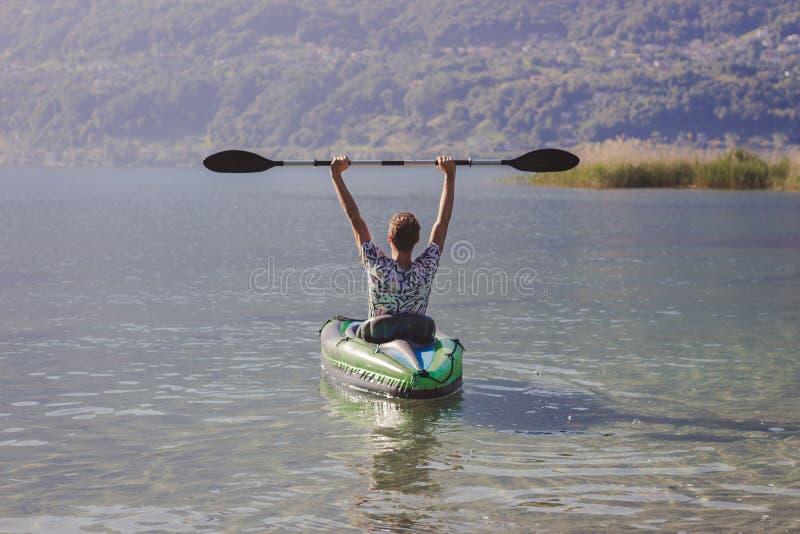 Homem novo que kayaking no lago fotos de stock