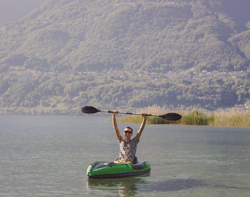 Homem novo que kayaking no lago foto de stock