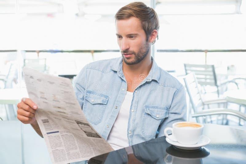 Homem novo que lê os jornais fotos de stock