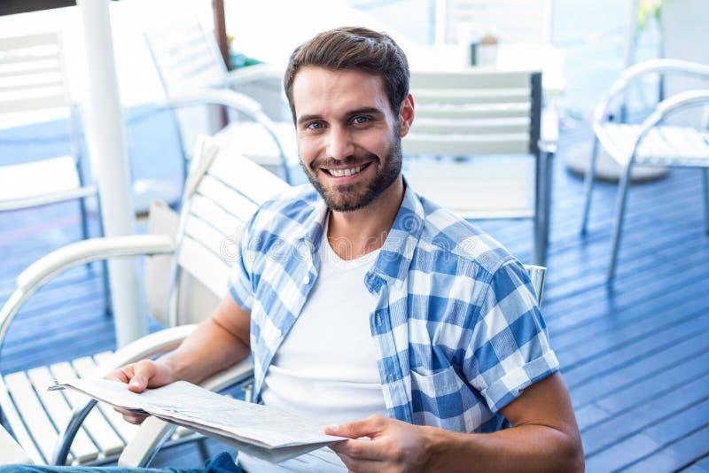 Homem novo que lê os jornais imagens de stock royalty free