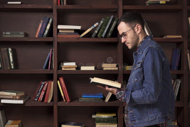Homem novo que lê um livro na biblioteca foto de stock royalty free