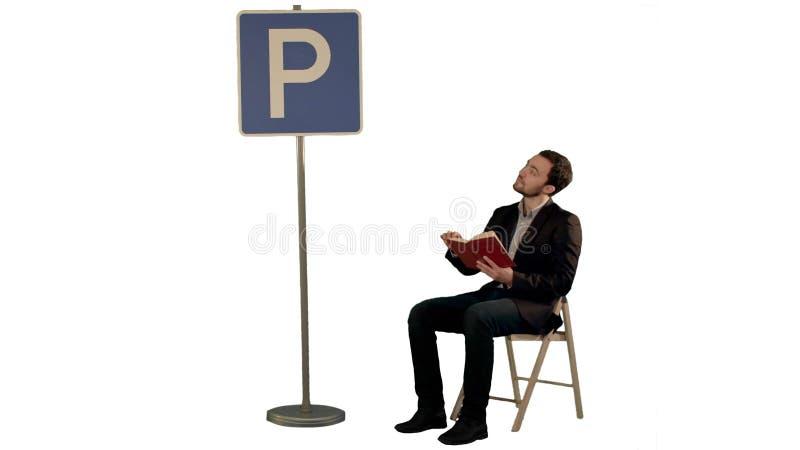 Homem novo que lê um livro perto do sinal do estacionamento no fundo branco isolado imagens de stock royalty free