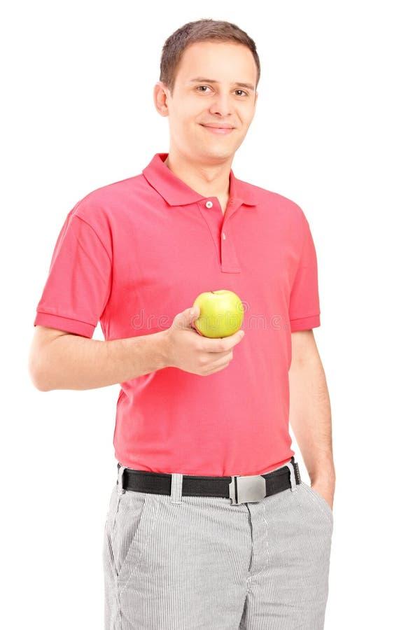 Homem novo que levanta com uma maçã em sua mão fotos de stock