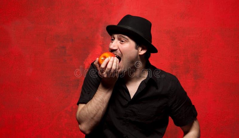 Homem novo que levanta e que come a maçã imagem de stock royalty free