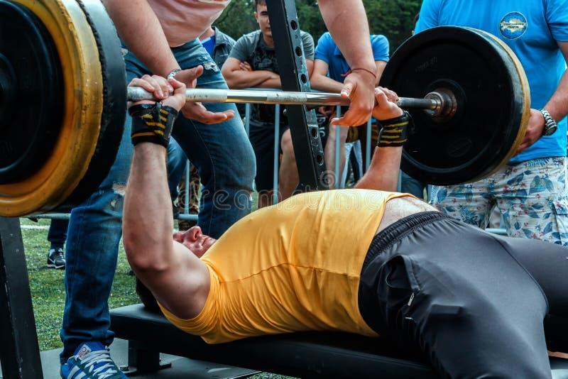 Homem novo que levanta o barbell na rua com instrutor weightlifting Esporte da rua fotos de stock royalty free