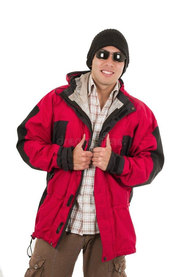 Homem novo que levanta o chapéu vermelho vestindo do revestimento do inverno e fotografia de stock royalty free