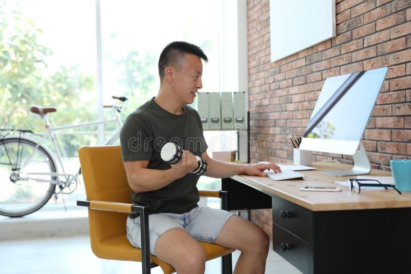 Homem novo que levanta peso e que usa o computador no escritório imagem de stock royalty free