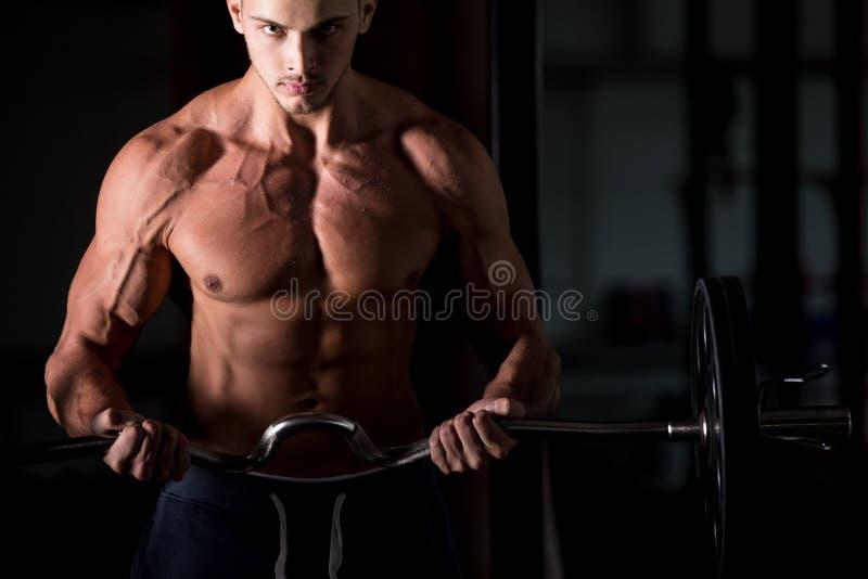 Homem novo que levanta um barbell no fitness center fotos de stock royalty free