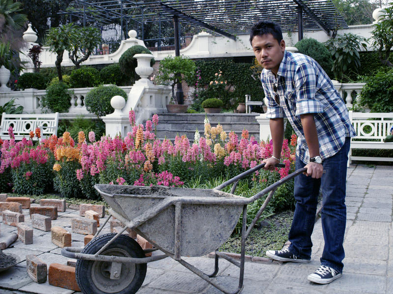 Homem novo que limpa o jardim foto de stock royalty free