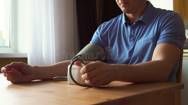 Homem novo que mede a pressão sanguínea em casa imagem de stock royalty free