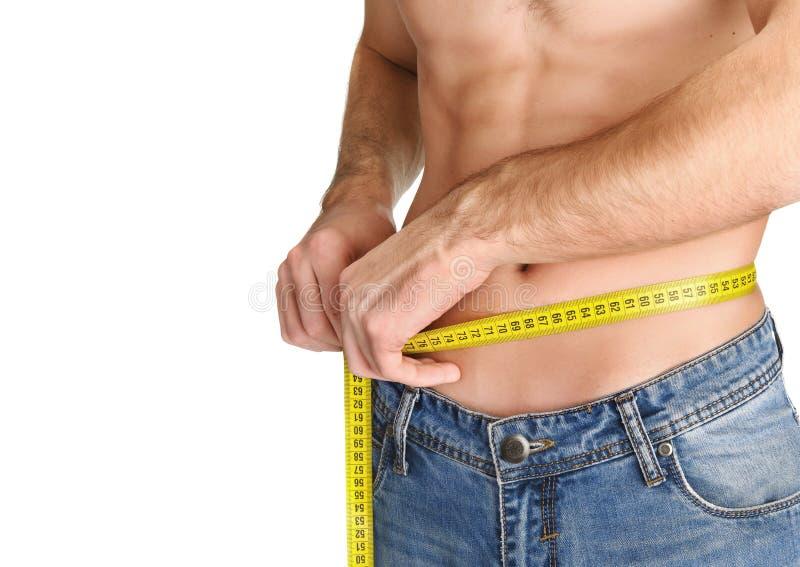 Homem novo que mede sua cintura imagens de stock