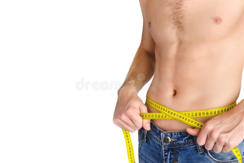 Homem novo que mede sua cintura foto de stock royalty free