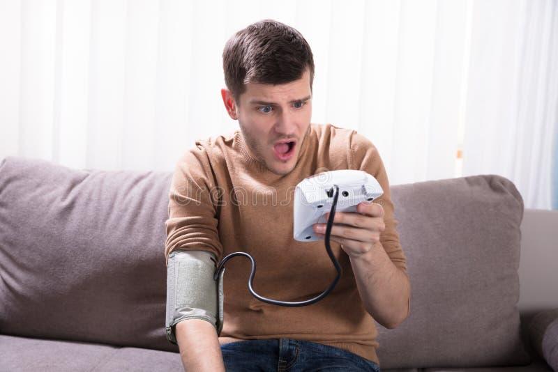 Homem novo que mede sua pressão sanguínea fotografia de stock