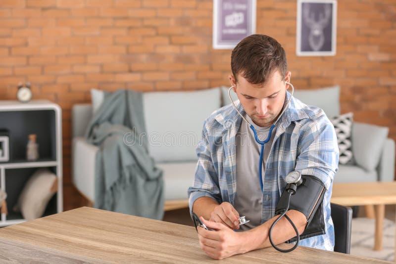 Homem novo que mede sua pressão sanguínea em casa fotos de stock