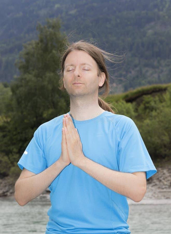 Homem novo que medita na pose de Namaste fora na natureza fotos de stock royalty free