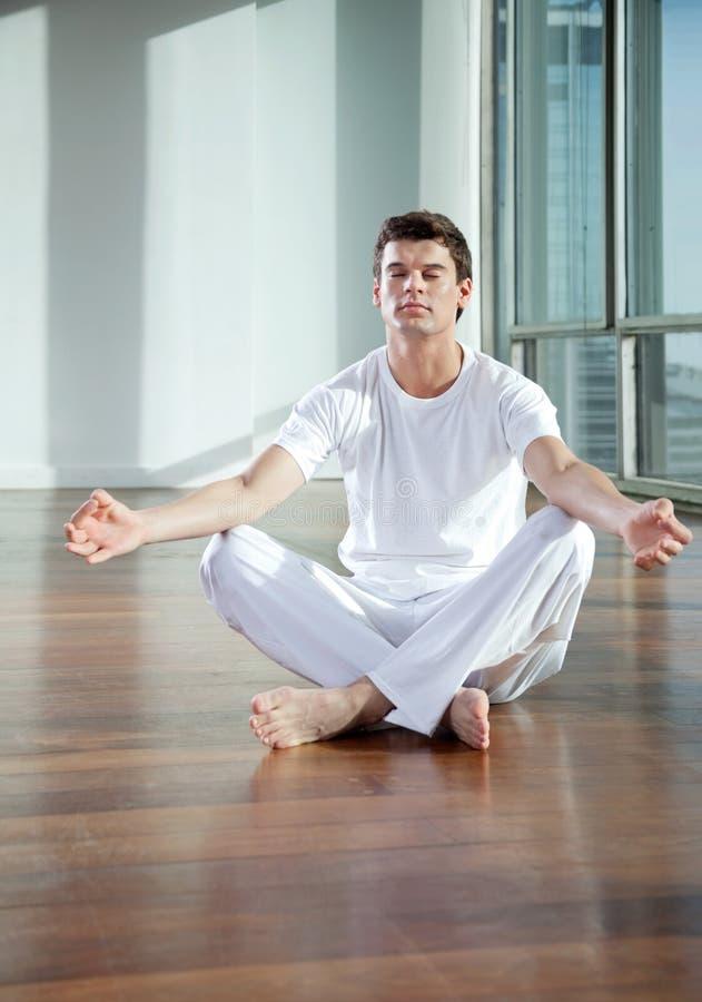 Homem novo que medita no Gym imagem de stock