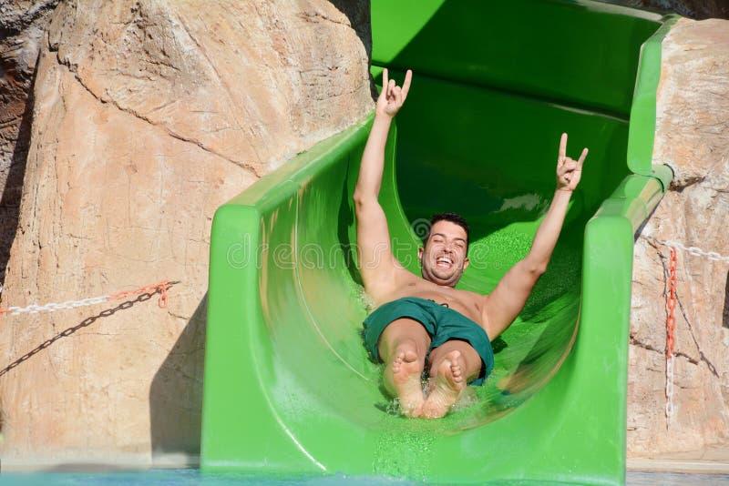 Homem novo que monta abaixo de um corrediça-homem da água que aprecia um passeio do tubo da água fotografia de stock royalty free