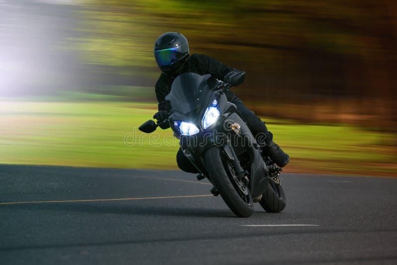 Homem novo que monta a motocicleta grande da bicicleta na maneira alta do asfalto contra fotografia de stock royalty free