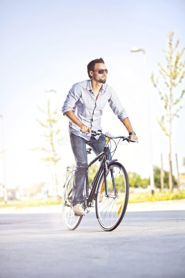Homem novo que monta uma bicicleta foto de stock royalty free