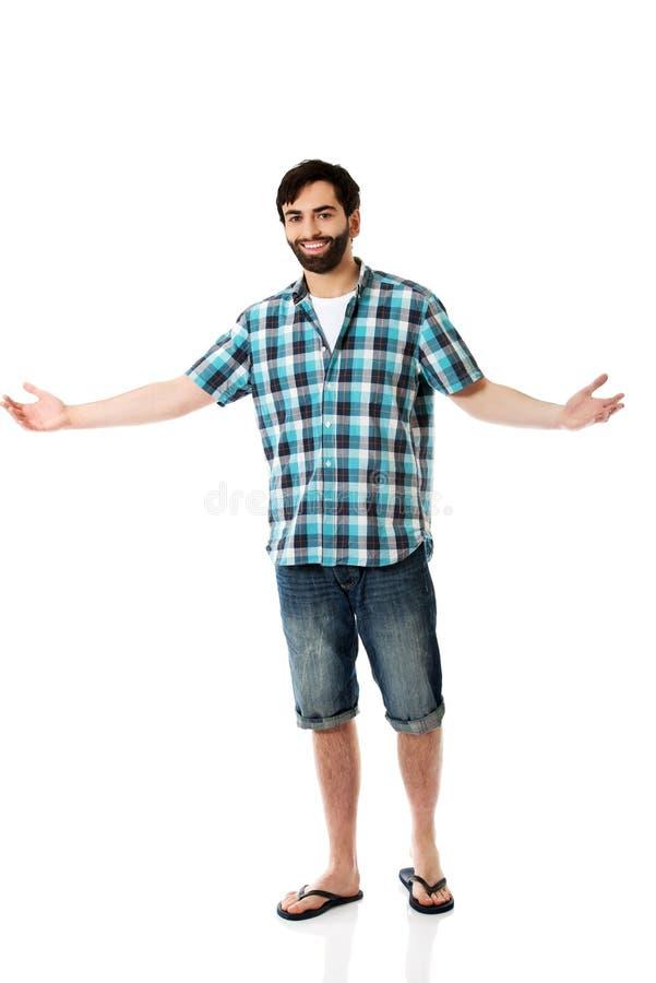 Homem novo que mostra algo nas mãos foto de stock royalty free