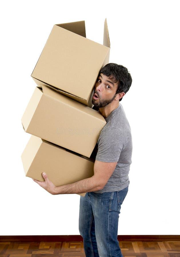 Homem novo que move-se em uma pilha levando da casa nova de caixas de cartão foto de stock royalty free