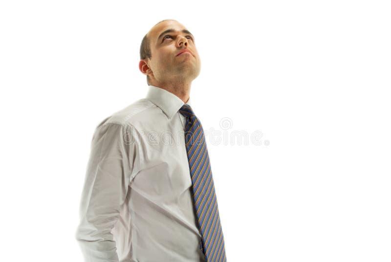 Homem novo que olha acima em um fundo branco imagem de stock