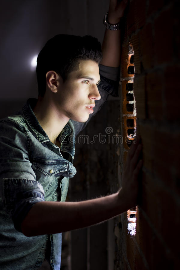 Homem novo que olha através do furo na parede de tijolo fotografia de stock royalty free