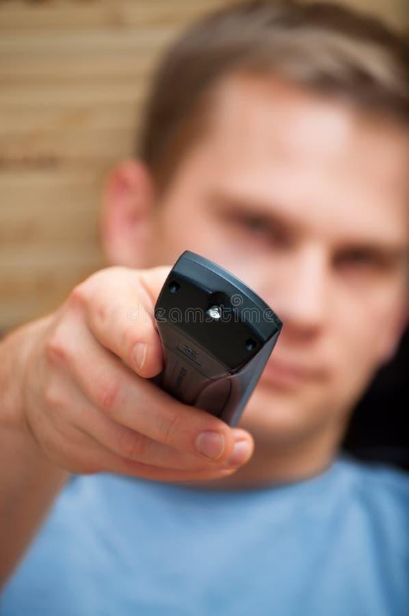 Homem novo que olha a câmera com telecontrole imagens de stock royalty free