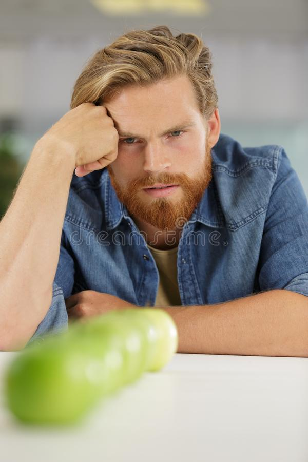 Homem novo que olha fixamente em maçãs da fileira foto de stock