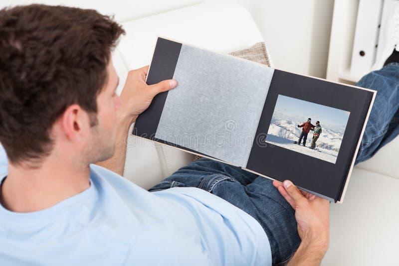 Homem novo que olha o álbum de fotografias fotos de stock royalty free