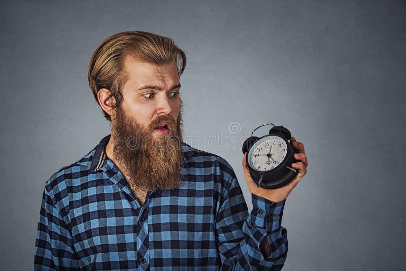 Homem novo que olha o despertador com o medo que é tarde fotografia de stock
