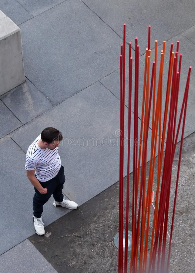 Homem novo que olha o projeto da arte perto da ponte do milênio em Denver, Colorado imagem de stock