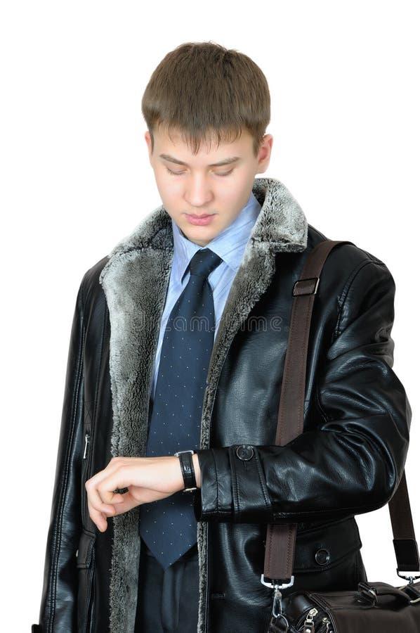 Homem novo que olha seu relógio de pulso fotos de stock