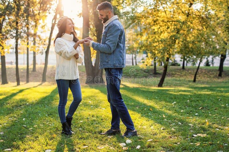 Homem novo que põe o anel de noivado sobre o dedo da noiva no parque do outono fotos de stock royalty free