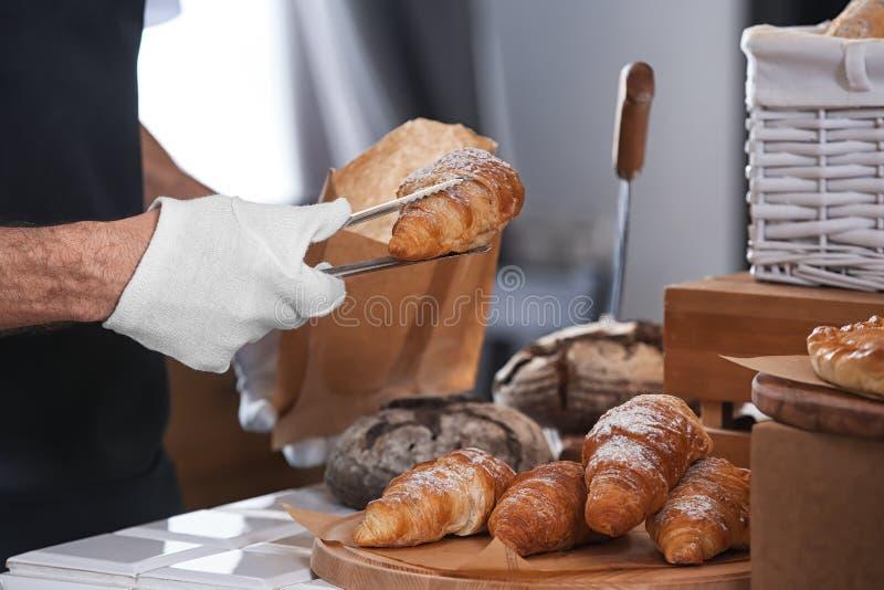 Homem novo que põe o croissant no saco de papel com os tenazes de brasa na padaria fotografia de stock