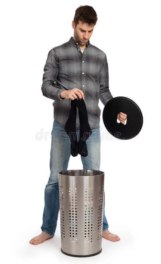 Homem novo que põe peúgas sujas em uma cesta de lavanderia fotografia de stock royalty free
