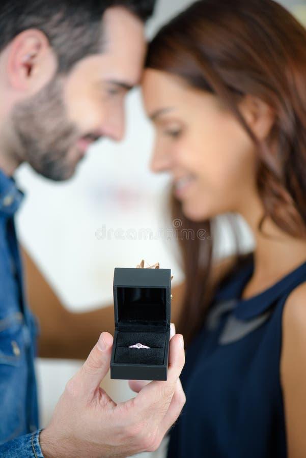 Homem novo que pede a menina bonita a mão imagens de stock royalty free