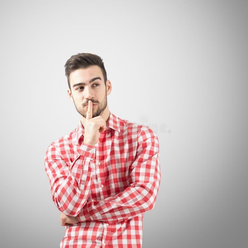 Homem novo que pensa com o indicador sobre sua boca imagens de stock