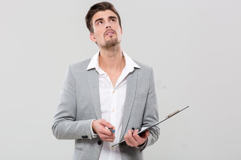 Homem novo que pensa guardando a prancheta imagens de stock