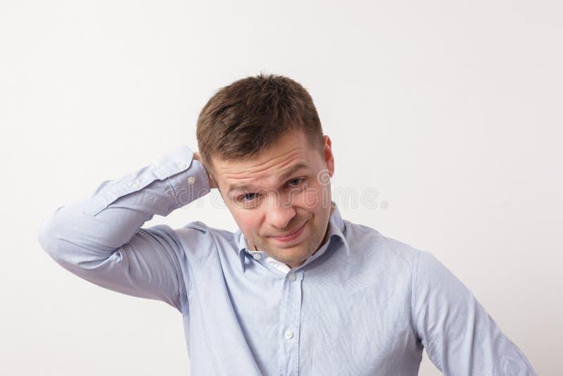 Homem novo que pensa sobre algo difícil, comprimindo seus bordos imagem de stock