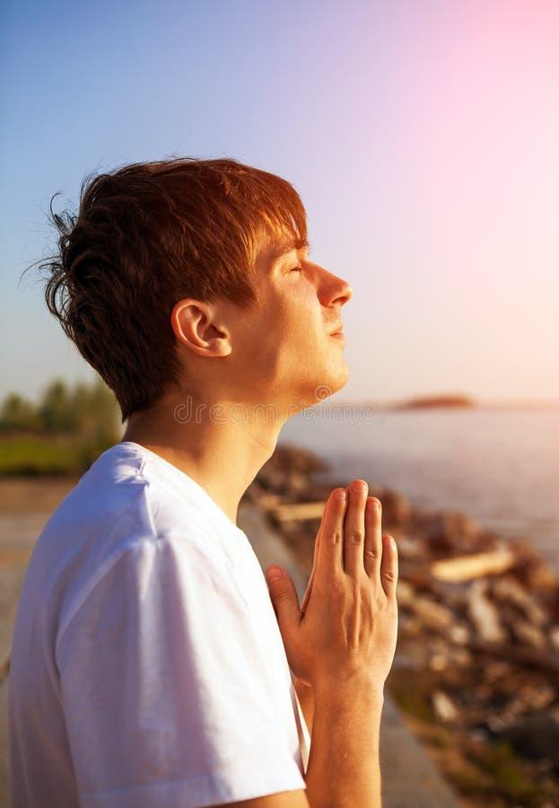 Homem novo que praying foto de stock