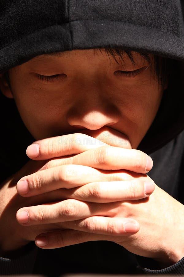 Homem novo que praying ao deus foto de stock royalty free