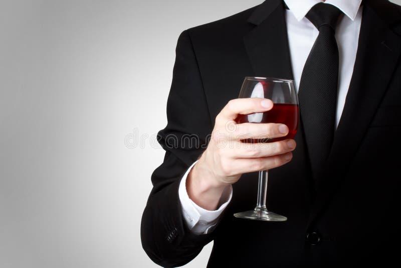 Homem novo que prende um vidro do vinho vermelho foto de stock royalty free