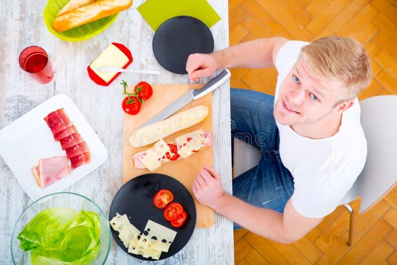 Homem novo que prepara um sanduíche imagem de stock